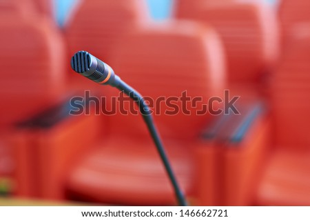 before a conference, the microphone in front of empty chairs. - stock photo