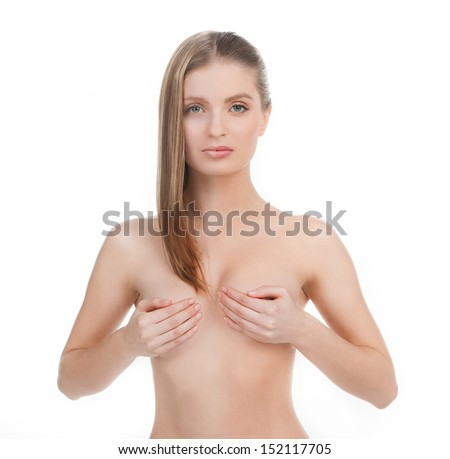 Before and After.  Beautiful young woman with make-up on the one part of face and without make-up on another covering her breast with hands while isolated on white - stock photo