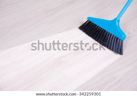before and aftet cleaning concept - blue broom sweeping parquet floor - stock photo