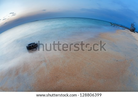 Before night on the white sand tropical beach with tire. Phuket. Thailand