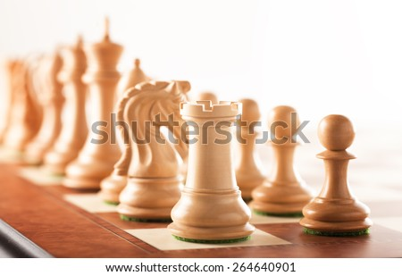 Before the battle - white chess pieces standing on a chessboard ready to fight - stock photo