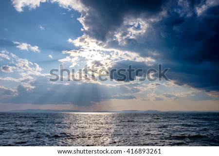 Before the storm. Dark moody sky over the gray sea. Ray of light through the cloud - stock photo