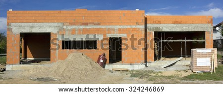 Began construction of the red brick no name mass production rural shed. Sunny day landscape. Panoramic image from several shots
