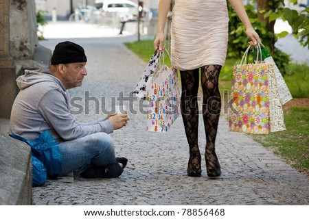 Beggar and a rich young woman with shopping bags - stock photo