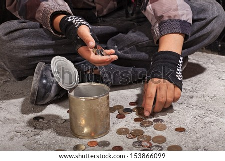 Beggar child counting coins sitting on damaged concrete floor - closeup on hands - stock photo