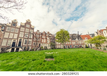 Begijnhof courtyard with  garden surrounded by historic houses in Amsterdam, Netherlands - stock photo