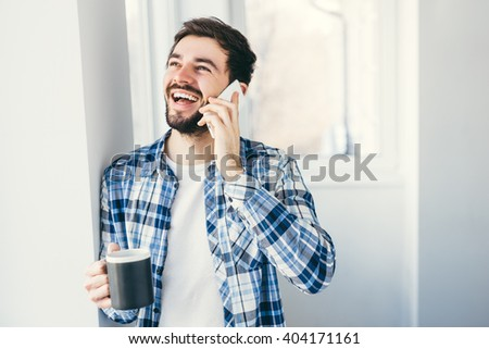 Begin your morning with cup of coffee. Handsome young man talking on mobile phone and holding cup of coffee - stock photo