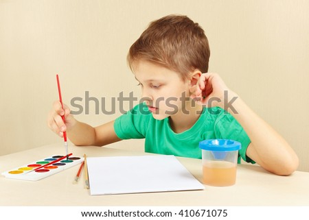 Beginner artist in a green shirt going to paint watercolors - stock photo