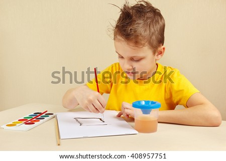 Beginner artist in a yellow shirt painting colors - stock photo