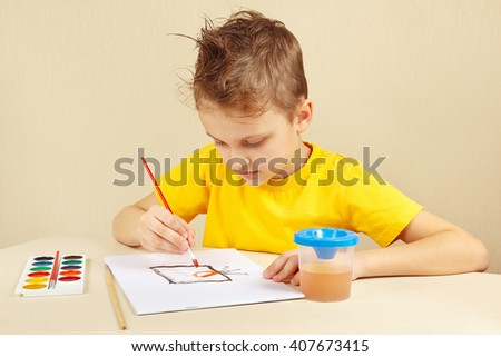 Beginner artist in a yellow shirt painting with watercolors - stock photo
