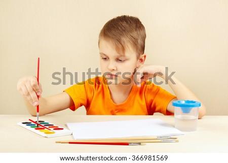 Beginner artist in an orange shirt going to paint watercolors - stock photo