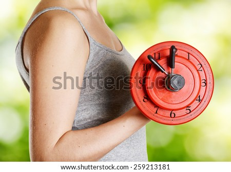 Beginner female athlete holding dumbbell with clock dial on nature background. Time for fitness. Trendy exercise for health and building muscle without fat. - stock photo