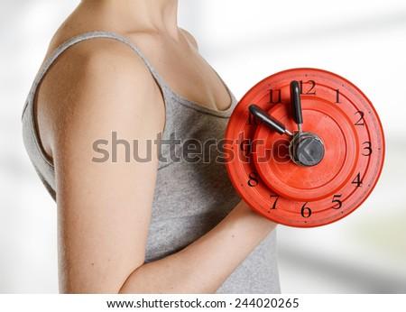 Beginner female athlete holding dumbbell with clock dial. Time for fitness. - stock photo