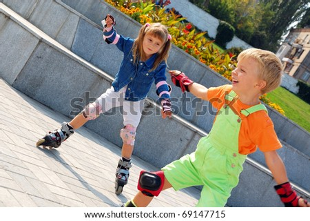 Beginners are learning in-line skating in the park, and having fun. - stock photo