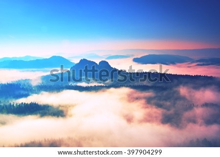 Beginning of spring. Fantastic dreamy sunrise above deep valley hidden in the rocky mountains . Beautiful spring misty day - stock photo