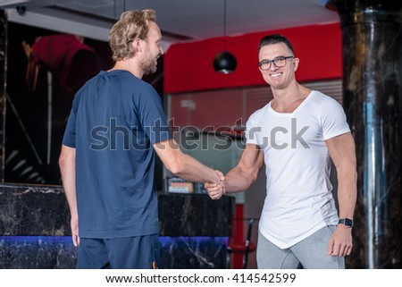 Beginning sports day. Nice coach and client shake hands with each other before a workout in the gym - stock photo