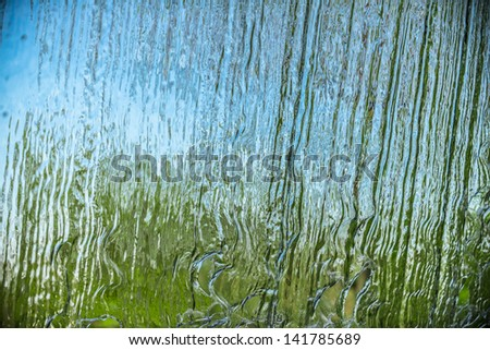 Behind a waterfall. A beautiful view of a blue sky and green trees through the falling water cascade. - stock photo