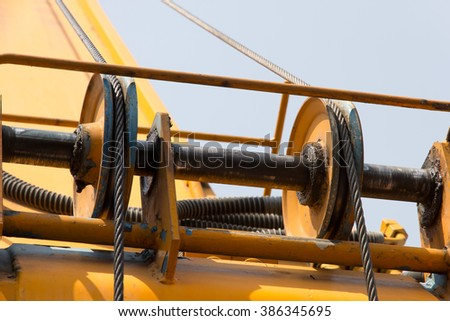 Behind Crane on steel ropes in site construction - stock photo
