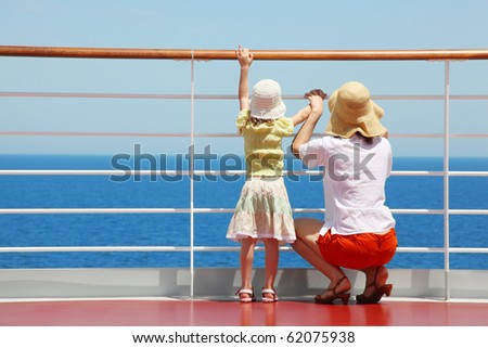 behind mother and her daughter standing on deck of yacht and they look far aboard - stock photo