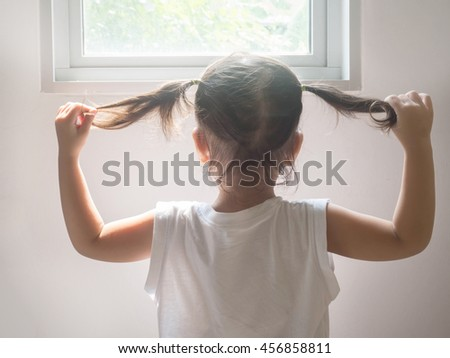 behind of girl holding her hair in hands near the window with soft light
