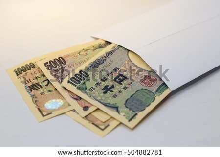 behind side of ten thousand yen japanese money in white envelope on table. Japanese yen bills in envelope with selective focus