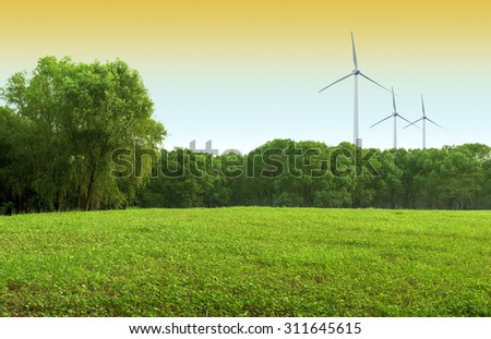 Behind the green lawns and trees, the wind turbine generators. - stock photo