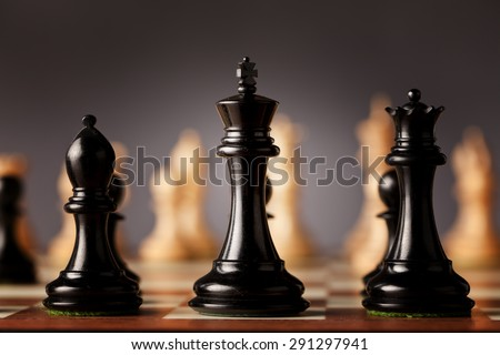 Behind the scenes - black chess king, queen and bishop in focus standing on a wooden chessboard facing the white chess pieces before the game - stock photo
