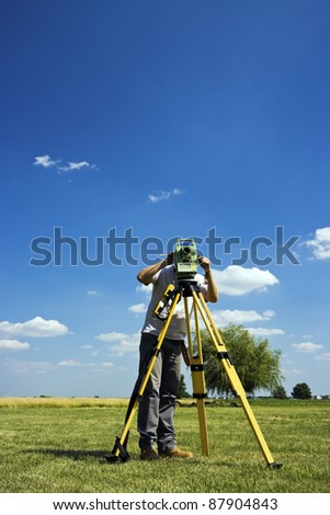 Behind Theodolite - land surveying in rural area. - stock photo