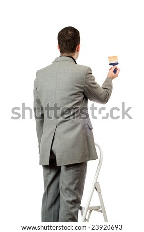 Behind view of a businessman painting something, isolated against a white background - stock photo