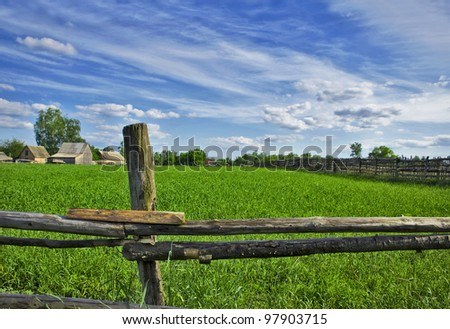 Behind village. Green grass behind a shabby wooden fence - stock photo