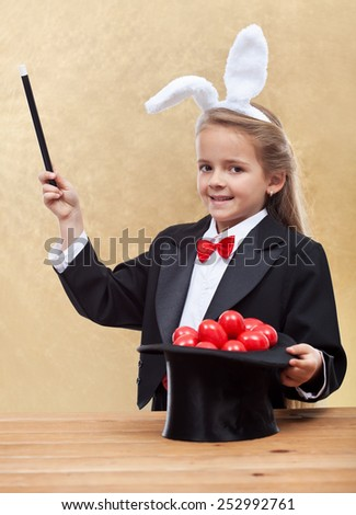 Behold the red easter eggs - little magician bunny girl with magic hat-shallow depth of field - stock photo