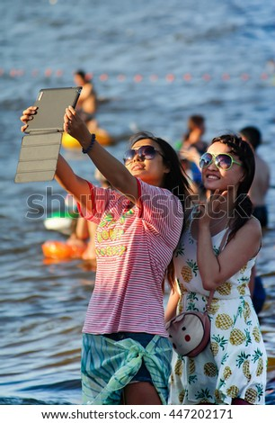 Beidaihe, China. August 9, 2012. Two young girls in sunglasses doing selfie on the computer tablet