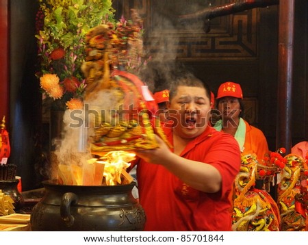 BEIGANG,TAIWAN-APRIL 21:Passing-stove ceremony in Beigang April 21, 2011. According to the custom of Taoism religion, an idol should come back to its' original temple to host this ceremony annually. - stock photo