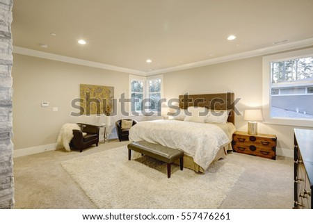 Beige and brown master bedroom boasts queen bed with taupe tufted headboard and bench. Beside the bed a vintage trunk nightstand next to sitting area with black leather armchairs. Northwest, USA