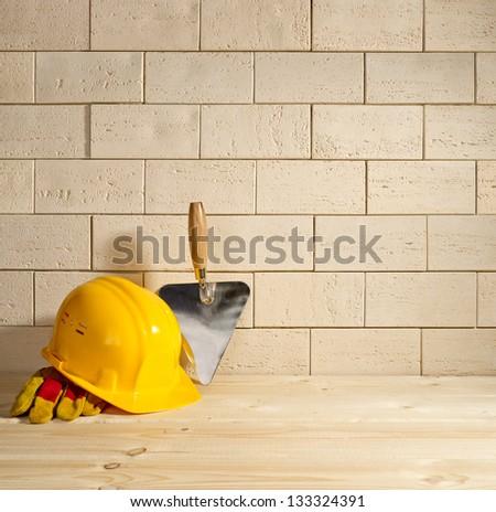beige brick background, trowel and helmet on a wooden floor - stock photo