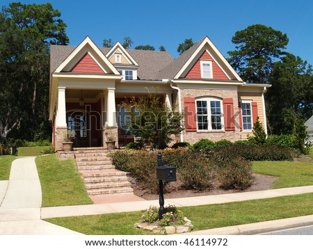 Beige brick home having peach and white trim with steps leading up to squares columns on the porch. - stock photo