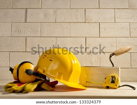 beige brick wall, yellow helmet and measuring tape on a wooden floor - stock photo