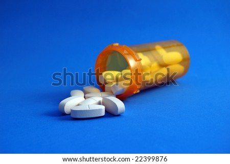Beige Calcium Pills Spilling Out of Bottle on Blue Background