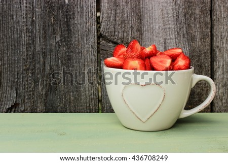Beige ceramic cup decorated with heart shape pattern full of ripe tasty strawberry on green wooden table in a rustic setting. Simple colorful composition with copy space - stock photo