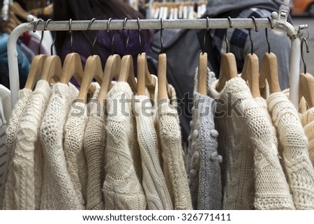 Beige color knitting sweater on clothes rack