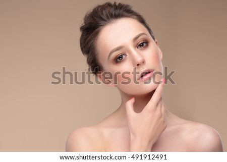 Beige color. Portrait of a woman with natural make-up. Hand near chin.