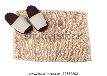 Beige doormat and brown house slippers - stock photo
