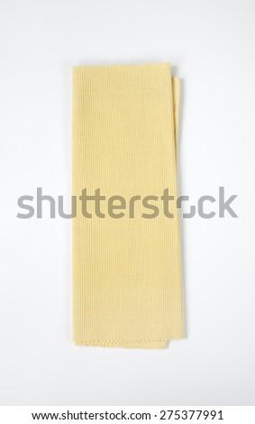 Beige folded napkin on white background - stock photo