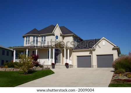 Beige home with beautiful landscaping - stock photo