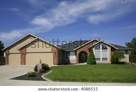 Beige home with red brick trim,green lawn and three car garage - stock photo