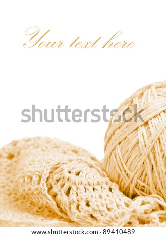 Beige knitted garment and a ball of thread isolated on white with space for text