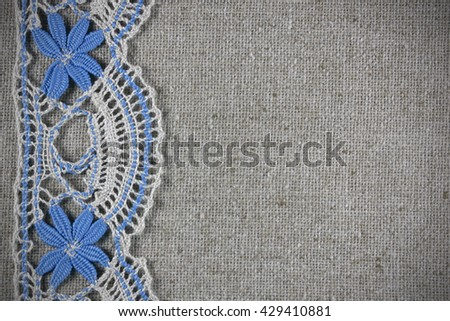 beige lace with blue flowers on burlap, postcard, background, with copy space for text - stock photo