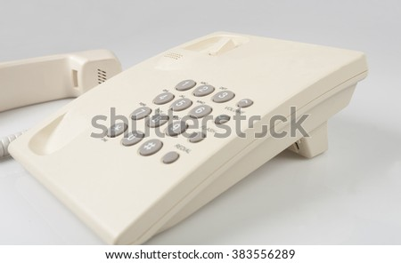 beige land line phone on gray background