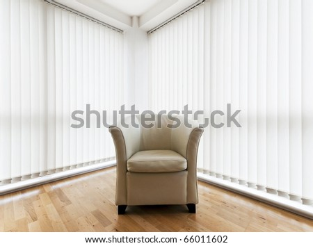 beige leather armchair in a room with wooden floor and vertical blinds - stock photo