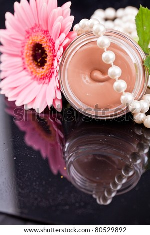 Beige liquid in the round glasses box with pearls,flowers and drops water.